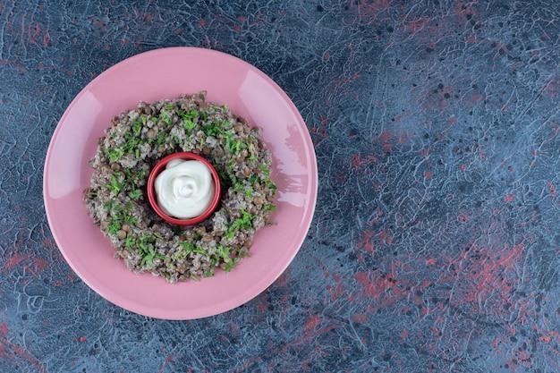 Een roze bord gehakt met doperwten en kruiden.