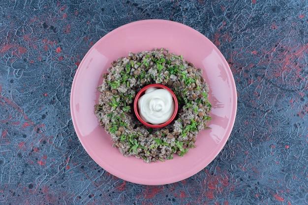 Een roze bord gehakt met doperwten en kruiden