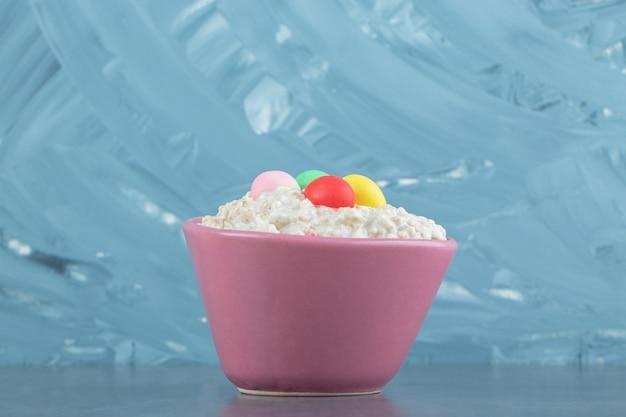 Een roze bord havermoutpap met kleurrijke snoepjes.