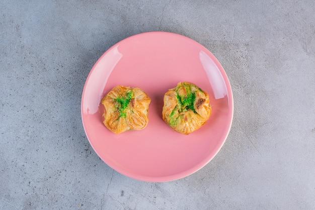 Een roze bord met twee heerlijke baklawa's op grijs