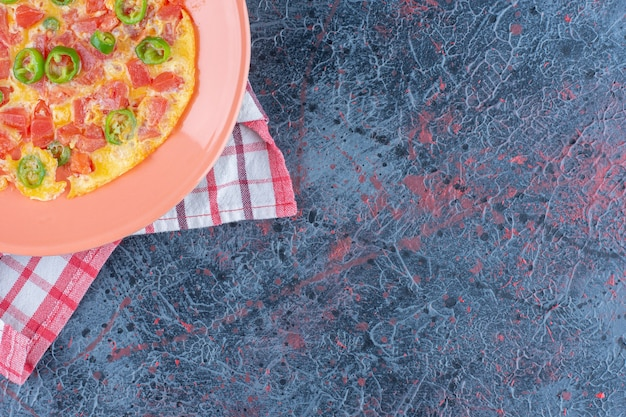 Een roze bord omelet met groenten.