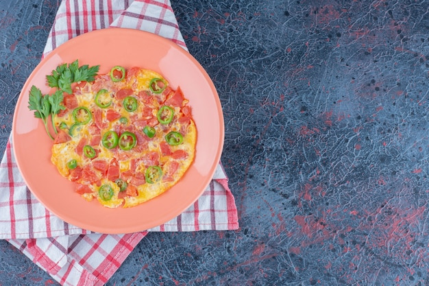 Een roze bord omelet met groenten