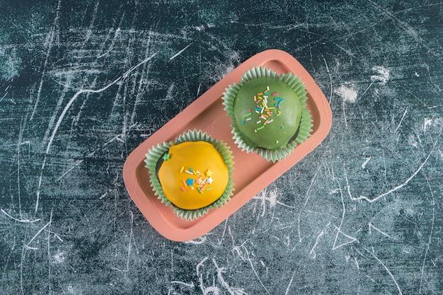 Een roze bord van cupcakes met een groene en gele coating.