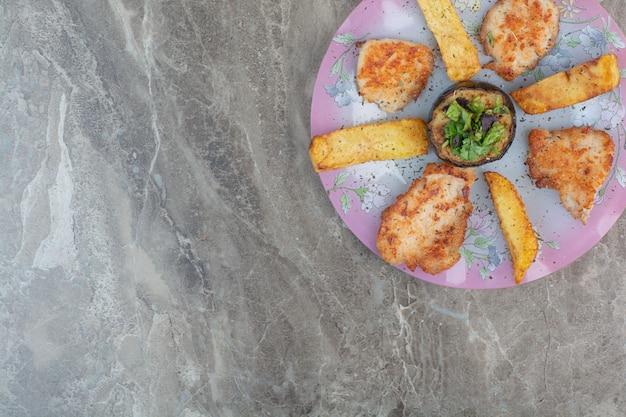 Een roze bord vol gebakken kip en aardappel met aubergine