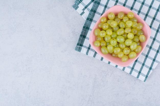 Een roze bord vol heerlijke groene druiven.