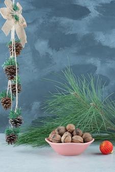 Een roze bord vol walnoten en rode kerstbal op marmeren achtergrond. hoge kwaliteit foto