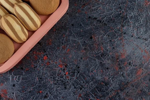 Een roze bord vol zoete gestreepte koekjes op een donkere tafel.