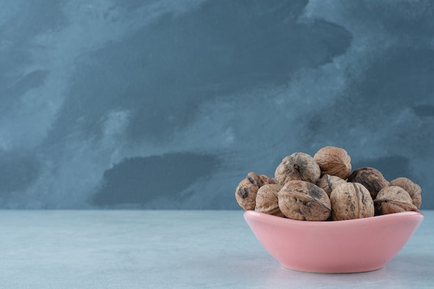 Een roze bordje vol noten op marmeren achtergrond. hoge kwaliteit foto