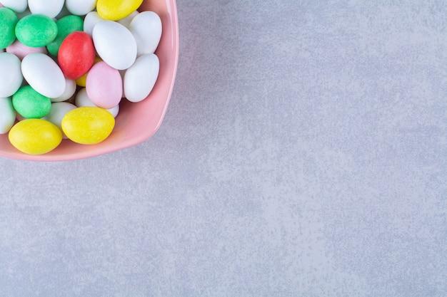 Een roze diep bord vol kleurrijke bonensnoepjes op grijze tafel.