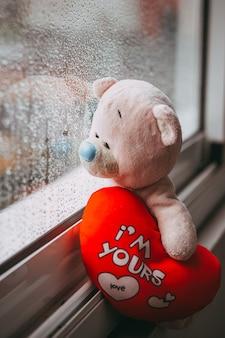Een roze droevige speelgoedbeer met een rood pluche hart zittend op de vensterbank regenachtige herfstdag regendruppels