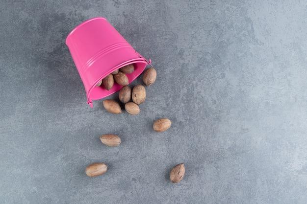Een roze emmer vol gezonde amandel