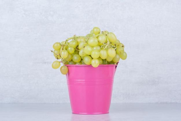 Een roze emmer vol groene zoete druiven