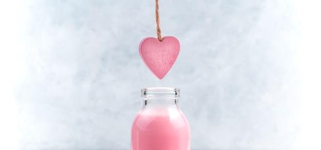 Een roze hart aan een touwtje hangt boven een fles roze milkshake. zijaanzicht, met ruimte om te kopiëren. het concept van valentijnsdag.