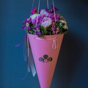 Een roze kartonnen boeket met seizoensgebonden zomerbloemen hing aan een studiomuur