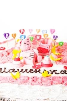 Een roze kinderverjaardagstaart met gelukkige verjaardagskaarsen