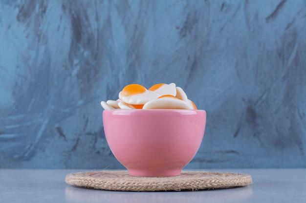 Een roze kom met zoete gelei-gebakken eieren op grijs oppervlak