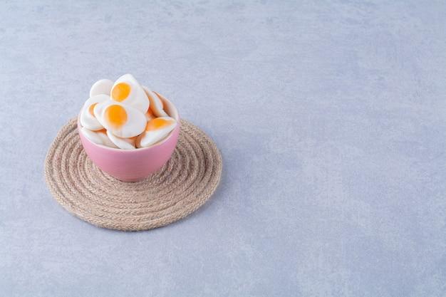 Een roze kom met zoete gelei-gebakken eieren op grijze tafel.