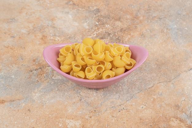 Een roze kom onvoorbereide macaroni op marmeren ruimte.
