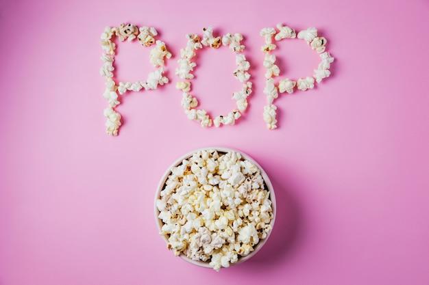 Een roze kom popcorn op roze oppervlak met woord pop gemaakt van maïs