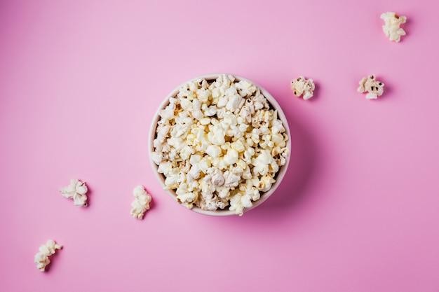 Een roze kom popcorn op roze oppervlak