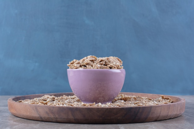 Een roze kom vol knapperige gezonde granen voor het ontbijt op een houten bord.