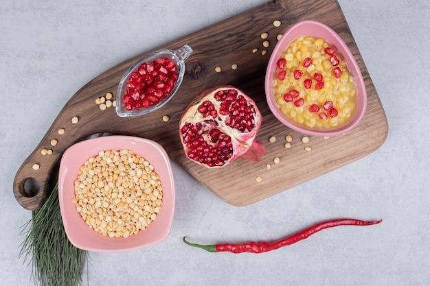 Een roze kom vol linzen met een schijfje granaatappel op een houten bord.