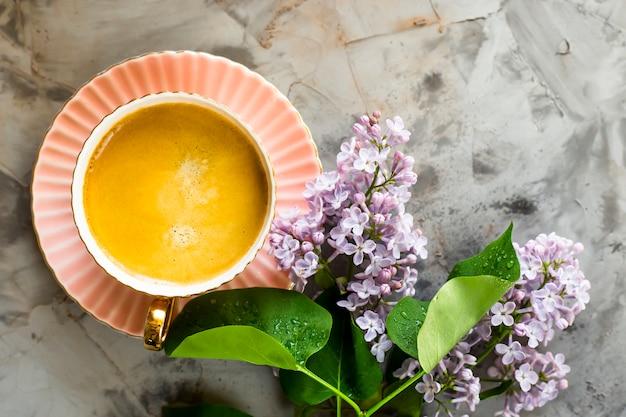 Een roze kop koffie met lila bloemen op een grijze betonnen tafel