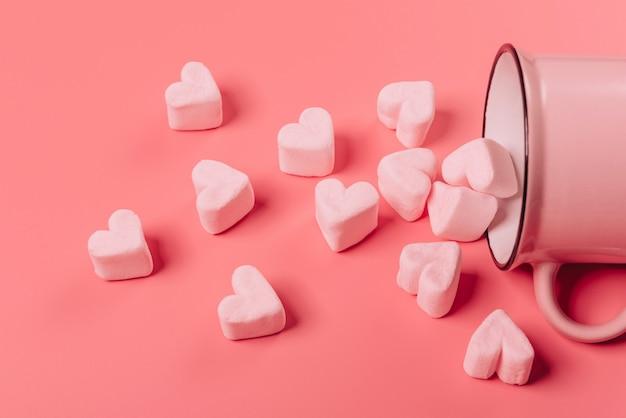 Een roze mok ligt op zijn kant tegen een roze oppervlak, lichtroze marshmallows worden er in de vorm van harten vanaf gestrooid