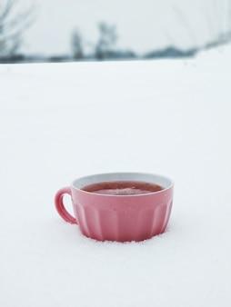 Een roze mok met hete frambozenthee op een besneeuwd winterveld. thee met jam verwarmt in de koude winter.