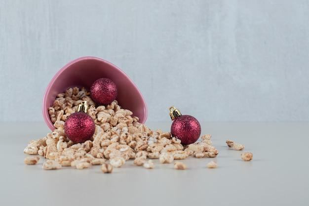 Een roze schaal vol gezonde granen met kerstballen.