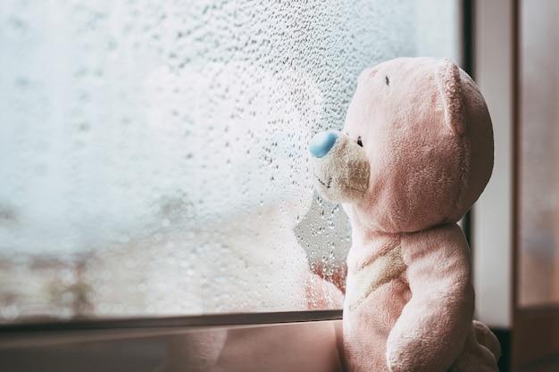 Een roze speelgoedbeer kijkt uit het raam en mist regenachtige herfstdag regendruppels op het raam