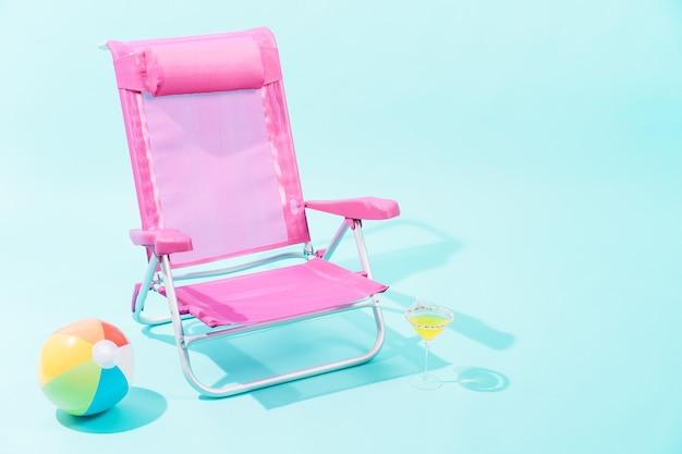 Een roze strandstoel met een veelkleurige strandbal
