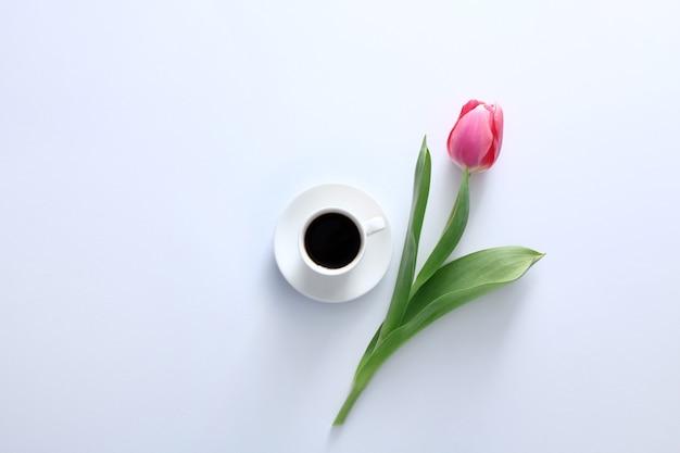 Een roze tulp en koffiekopje op witte achtergrond bovenaanzicht plat lag