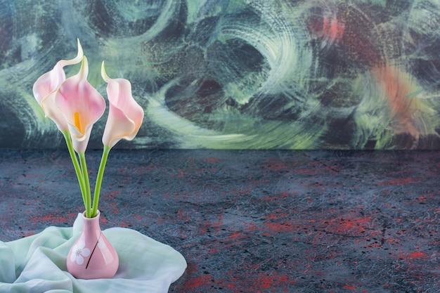 Een roze vaas vol calla bloemen op tafelkleed.