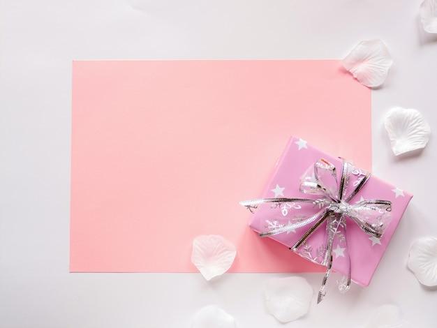 Een roze vel papier en een geschenkdoos