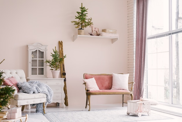Een roze vintage bank met kussens staat bij het raam in de woonkamer of kinderkamer, versierd voor kerstmis of nieuwjaar, in huis. minimalistisch interieur