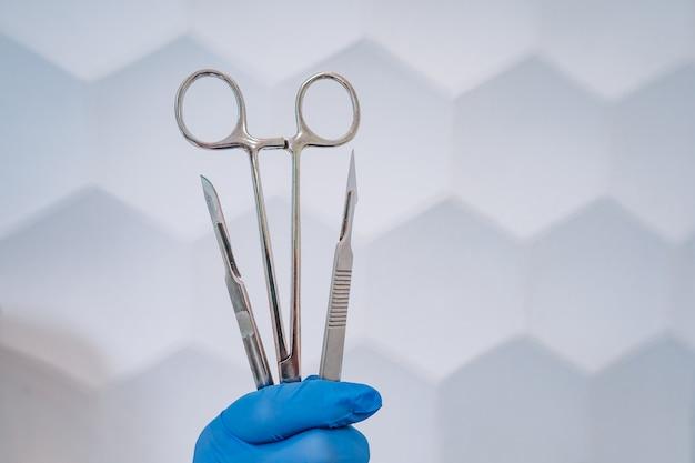 Een rubberen handschoenenhand houdt twee scalpels en een klem vast