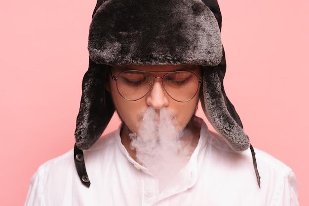 Een russische man met een traditionele hoed rookt een waterpijp en geniet ervan