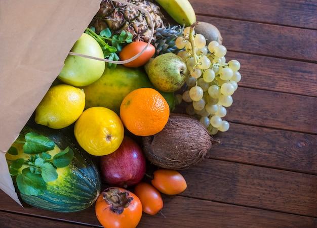 Een rustieke houten tafel met een papieren zak vol vers geplukt fruit.