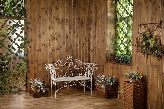 Een rustieke kamer met een smeedijzeren bank, houten lambrisering en bloemen.