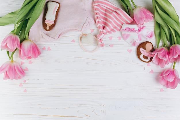 Een samenstelling voor pasgeborenen op een houten witte achtergrond met kleren.