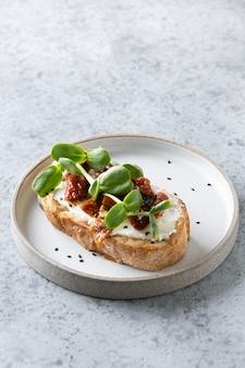 Een sandwich met radijs microgreens en zongedroogde tomaten op grijs.