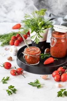Een saus van verse rode tomaten in een glazen pot op een zwarte plaat. takje verse kerstomaatjes, knoflook, hete peper, dille en peterselie op een witte tafel. een blikje zelfgemaakte ketchup