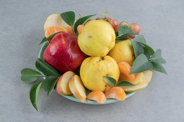 Een schaal met een stapel fruit op marmer