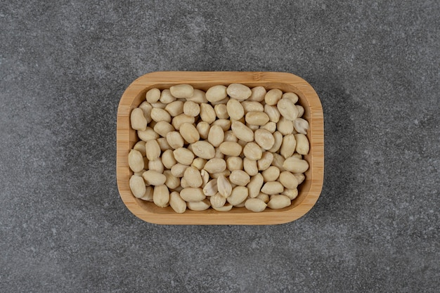 Een schaal met schelploze pinda's op het marmeren oppervlak
