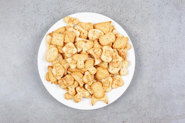 Een schaal vol knapperige crackers op een marmeren ondergrond