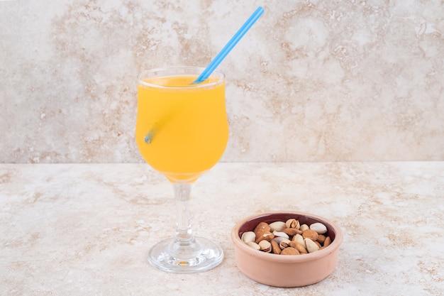 Een schaaltje met amandelen en pistachenoten en een glas sap