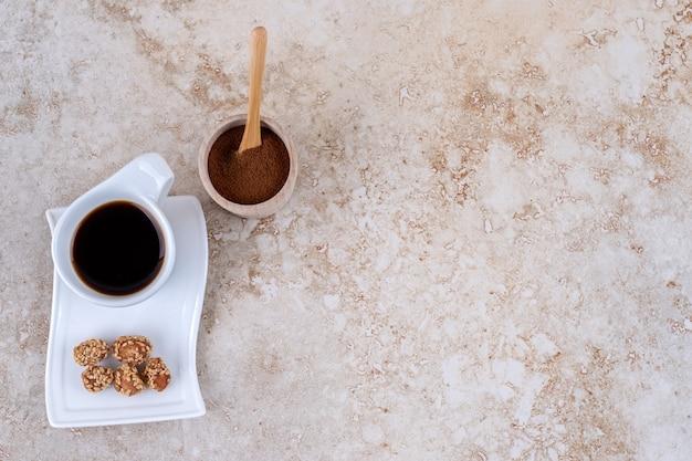 Een schaaltje met gemalen koffiepoeder, een kopje koffie en geglazuurde pinda's