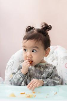 Een schattig aziatisch babymeisje zittend op de eettafel eet zelf broccoli, baby led weaning concept