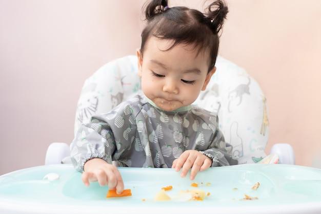 Een schattig aziatisch meisje dat op de eettafel zit, oefent om zelf te eten, baby-led weaning-concept
